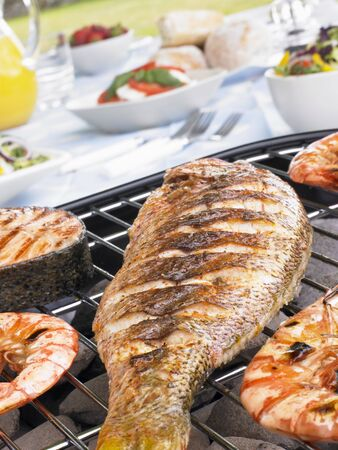 Fish And Prawns Cooking On A Grill photo