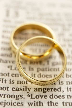 Two Wedding Rings Resting On A  Bible Page photo