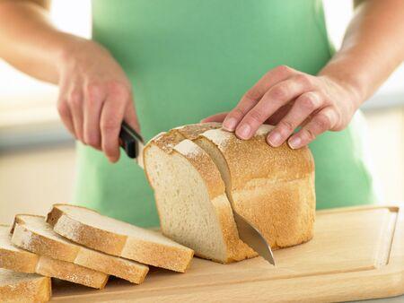haciendo pan: Una mujer de corte en rodajas de pan blanco Pan