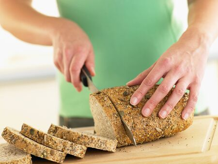 Woman Slicing Mixed Grain Bread photo