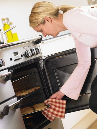 Woman Taking Cookies Out Of Oven Stock Photo - 4638705