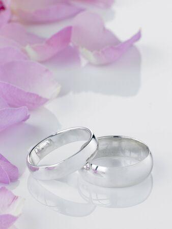 bodas de plata: Plata Anillos de boda al lado de p�talos de flores