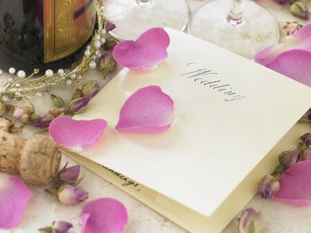 Wedding Invitation Next To Champagne Bottle Surrounded By Flower Petals photo