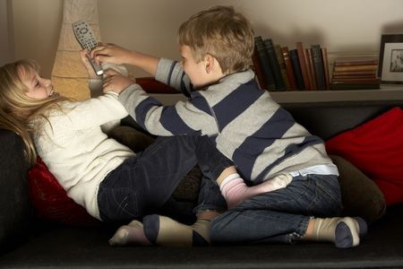 Brother And Sister Fighting Over Remote Control photo