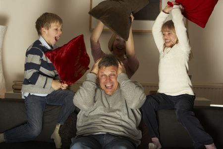Parents And Two Children In Pillow Fight photo