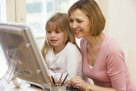 Woman And Daughter Using Computer photo