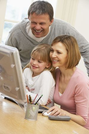 using computer: Couple And Daughter Using Computer