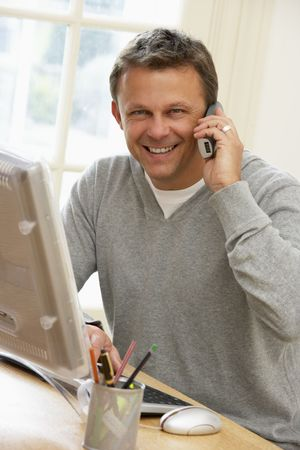 comunication: Man Using Computer And Talking On Phone