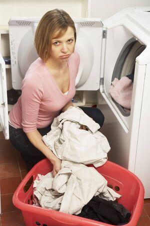 Unhappy Woman Doing Laundry photo