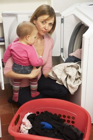 kneeling woman: Woman Doing Laundry And Holding Baby Daughter