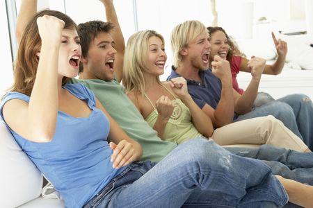 personas viendo tv: Amigos viendo un juego de Televisi�n Foto de archivo
