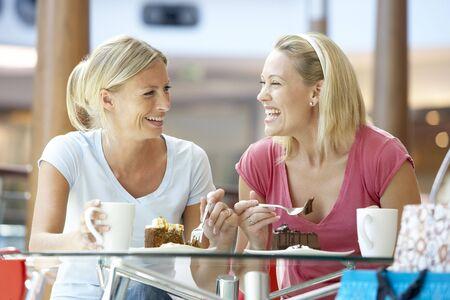 dos personas conversando: Mujeres Amigos almorzando juntos en el Mall