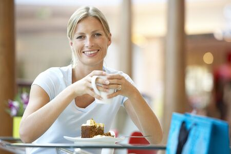 Woman Eating A Piece Of Cake At The Mall photo