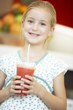 berry smoothie: Young Girl Drinking A Berry Smoothie Stock Photo