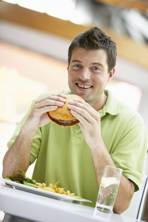 food court: Man Eating Lunch At A Cafe Stock Photo