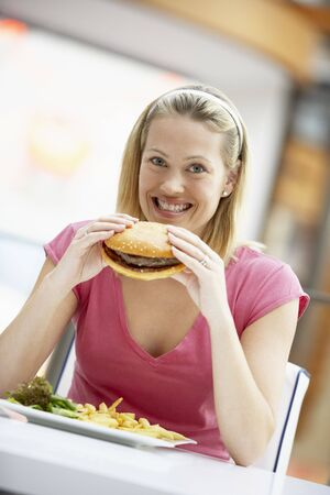 shopping binge: Woman Eating Lunch At A Cafe Stock Photo