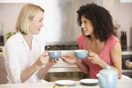 Female Friends Enjoying Tea And Cookies At Home Stock Photo - 4645092