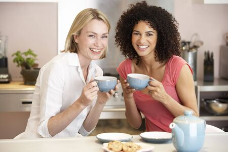 mid afternoon: Female Friends Enjoying Tea And Cookies At Home