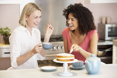 mid afternoon: Female Friends Enjoying Tea And Cake At Home