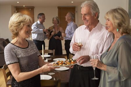 entertaining: Woman Serving Hors Doeuvres To Her Guests At A Dinner Party