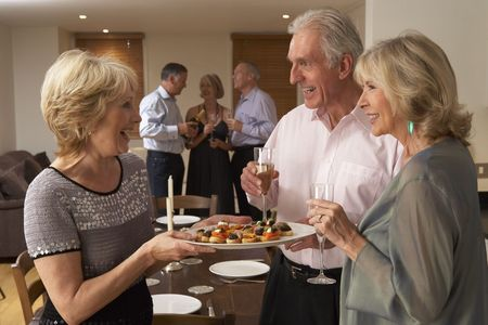 Woman Serving Hors Doeuvres To Her Guests At A Dinner Party photo