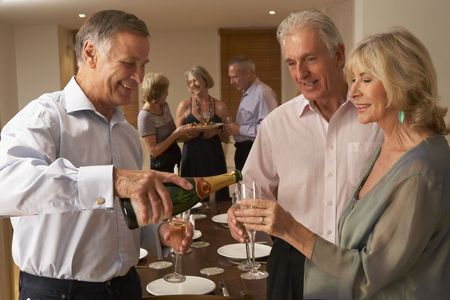 Man Serving Champagne To His Guests At A Dinner Party photo