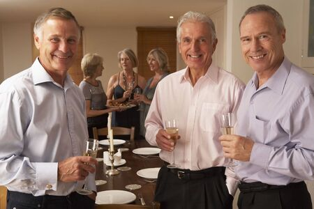 Friends Enjoying A Glass Of Champagne At A Dinner Party photo