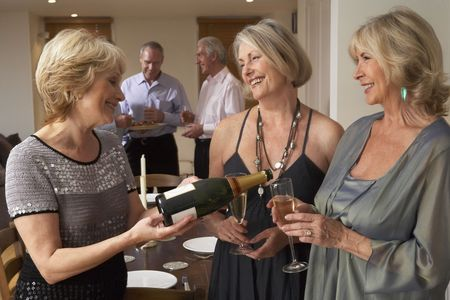 Woman Serving Champagne To Her Guests At A Dinner Party photo