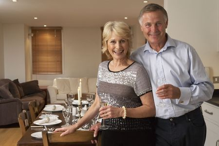 hosts: Couple Throwing A Dinner Party Stock Photo