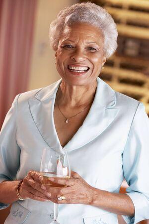 one senior adult woman: Habiendo mujer un vaso de vino en un bar