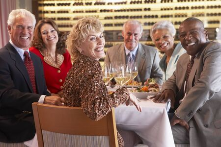 socializando: Amigos a cenar juntos en un restaurante Foto de archivo