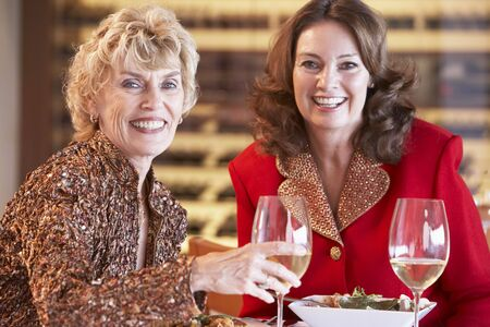older women: Friends Having Dinner Together At A Restaurant