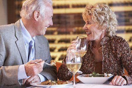 entertaining: Senior Couple Having Dinner Together At A Restaurant Stock Photo