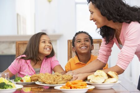 family dinner: Mother Serving A Meal To Her Children At Home