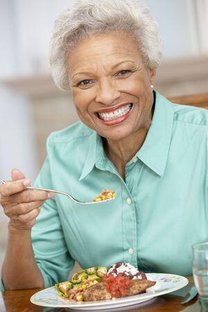 one senior adult woman: Mujer disfrutar de una comida en el hogar