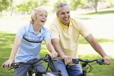 Father And Son Cycling Through A Park photo