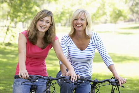 13 year old: Mother And Daughter Cycling Through A Park