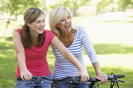 teen aged: Mother And Daughter Cycling Through A Park