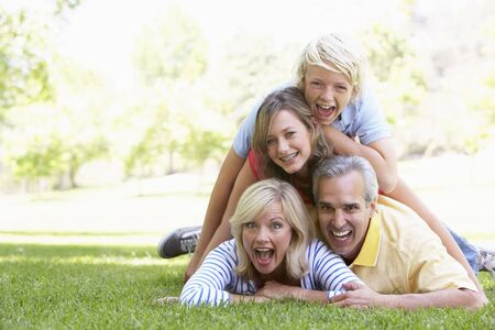 Family Lying On Top Of Each Other In A Park photo