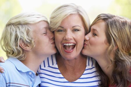 Woman Being Kissed By Her Teenage Children photo