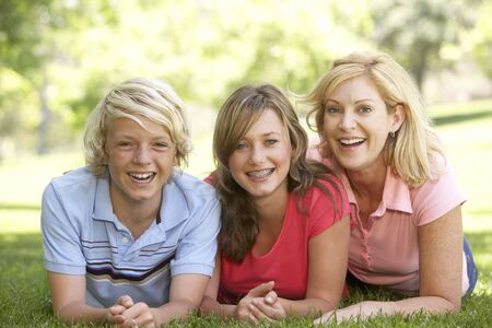 Woman And Her Teenage Children Lying On Grass photo