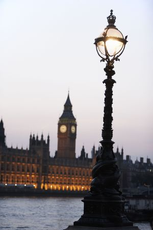south london: Old-Fashioned Street Lamp With Houses Of Parliament Illuminated In The Background, London, England Stock Photo