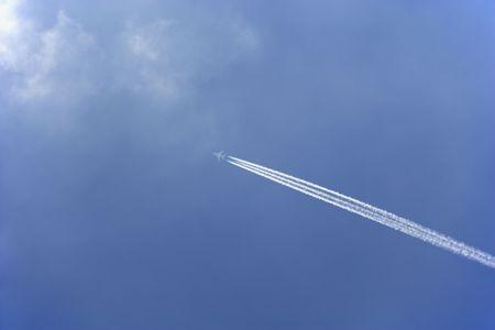 plan éloigné: Trail Blanc de condensation de A Commercial Airplane As It Flies Across A Blue Sky Banque d'images