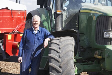 Driver Standing In Front Of Tractor photo