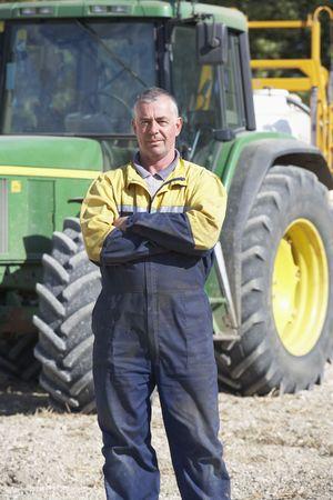 granjero: Conductor de pie frente a tractor Foto de archivo