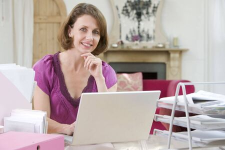 Woman sitting at her desk using laptop photo