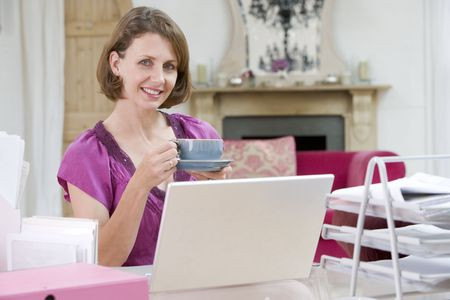 Woman drinking coffee at her desk photo
