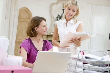 Women looking at paperwork together photo