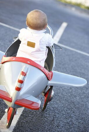 Baby Girl Riding In Toy Aeroplane photo