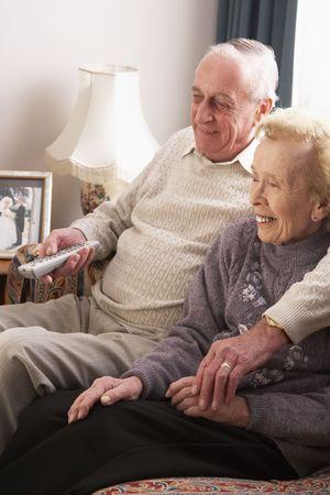 pareja viendo tv: Superior de la pareja ver televisi�n en el hogar Foto de archivo